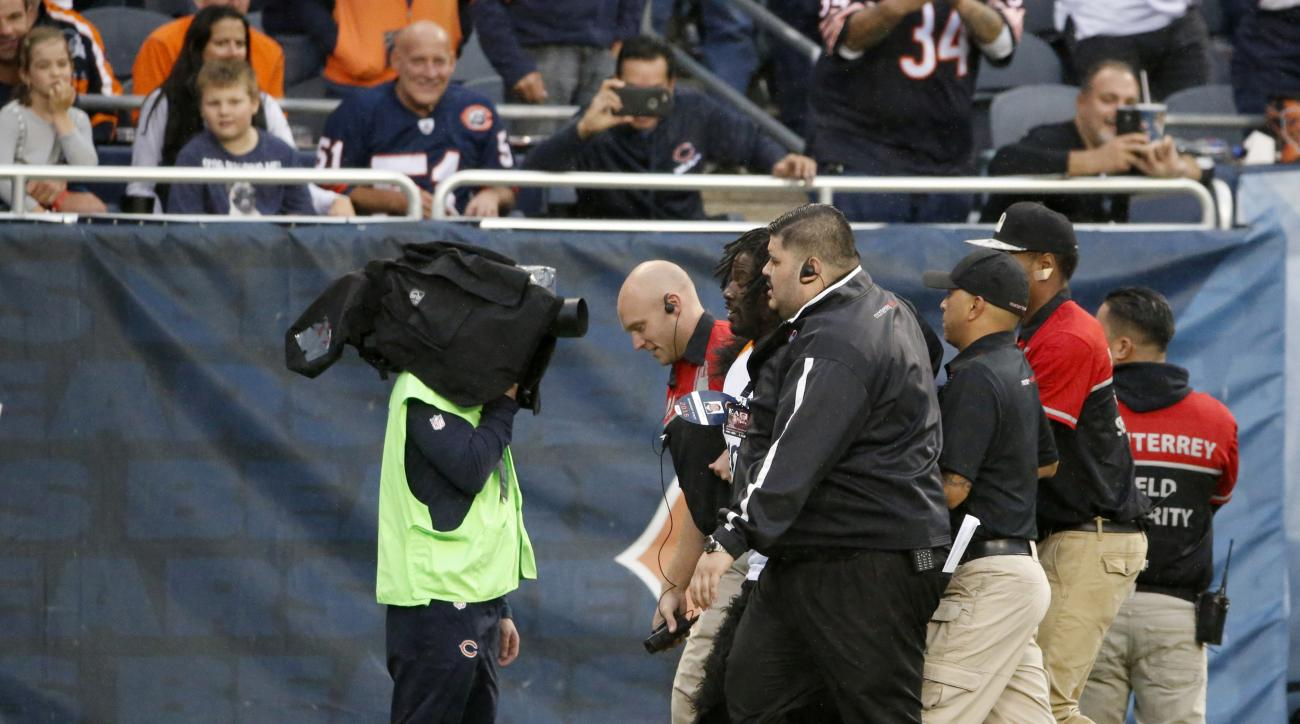 Security guards escort a fan off the field who ran down on the field during the second half of an NFL football game between the Chicago Bears and the Detroit Lions, Sunday, Oct. 2, 2016, in Chicago. (AP Photo/Nam Y. Huh)