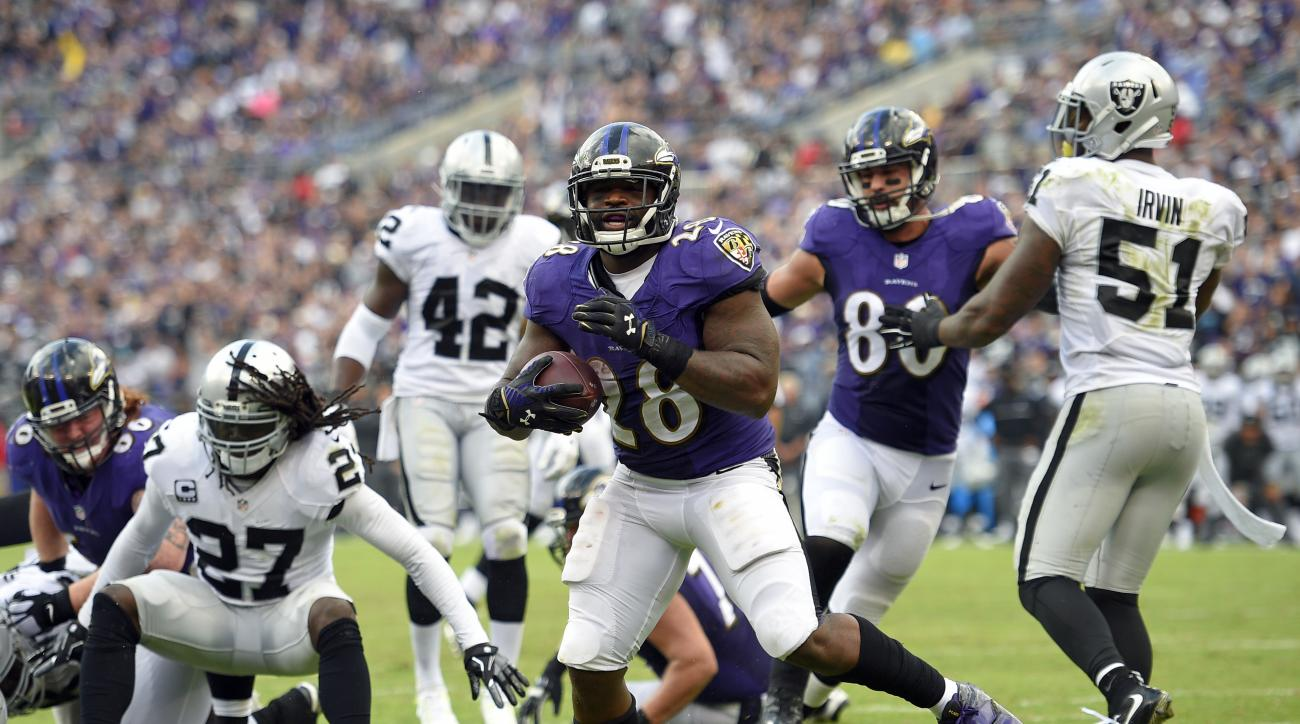 Baltimore Ravens running back Terrance West, center, scores a touchdown in the second half of an NFL football game against the Oakland Raiders, Sunday, Oct. 2, 2016, in Baltimore. (AP Photo/Nick Wass)