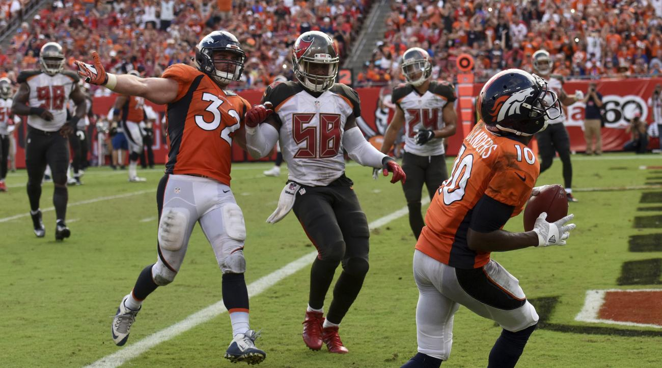 Denver Broncos wide receiver Emmanuel Sanders (10) pulls in a 5-yard touchdown pass as fullback Andy Janovich (32) blocks Tampa Bay Buccaneers middle linebacker Kwon Alexander (58) during the fourth quarter of an NFL football game Sunday, Oct. 2, 2016, in