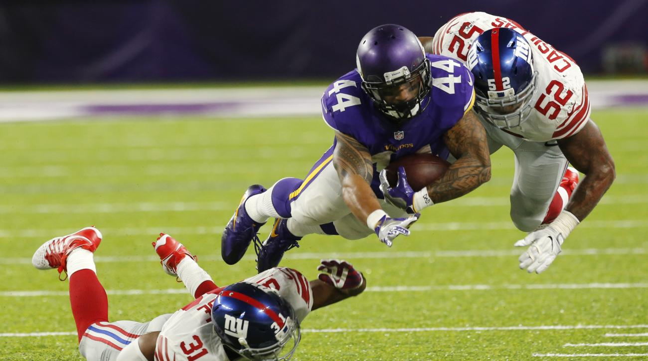 Minnesota Vikings running back Matt Asiata (44) dives for extra yardage between New York Giants defenders Trevin Wade, left, and Jonathan Casillas (52) during the second half of an NFL football game, Monday, Oct. 3, 2016, in Minneapolis. (AP Photo/Jim Mon