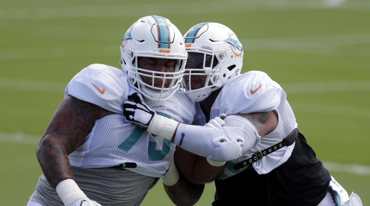 Miami Dolphins center Mike Pouncey, right, does drills against guard Jamil Douglas, left, during practice at the Miami Dolphins training facility, Tuesday, Oct. 4, 2016, in Davie, Fla. Pouncey returned Tuesday after missing the first four games of the sea