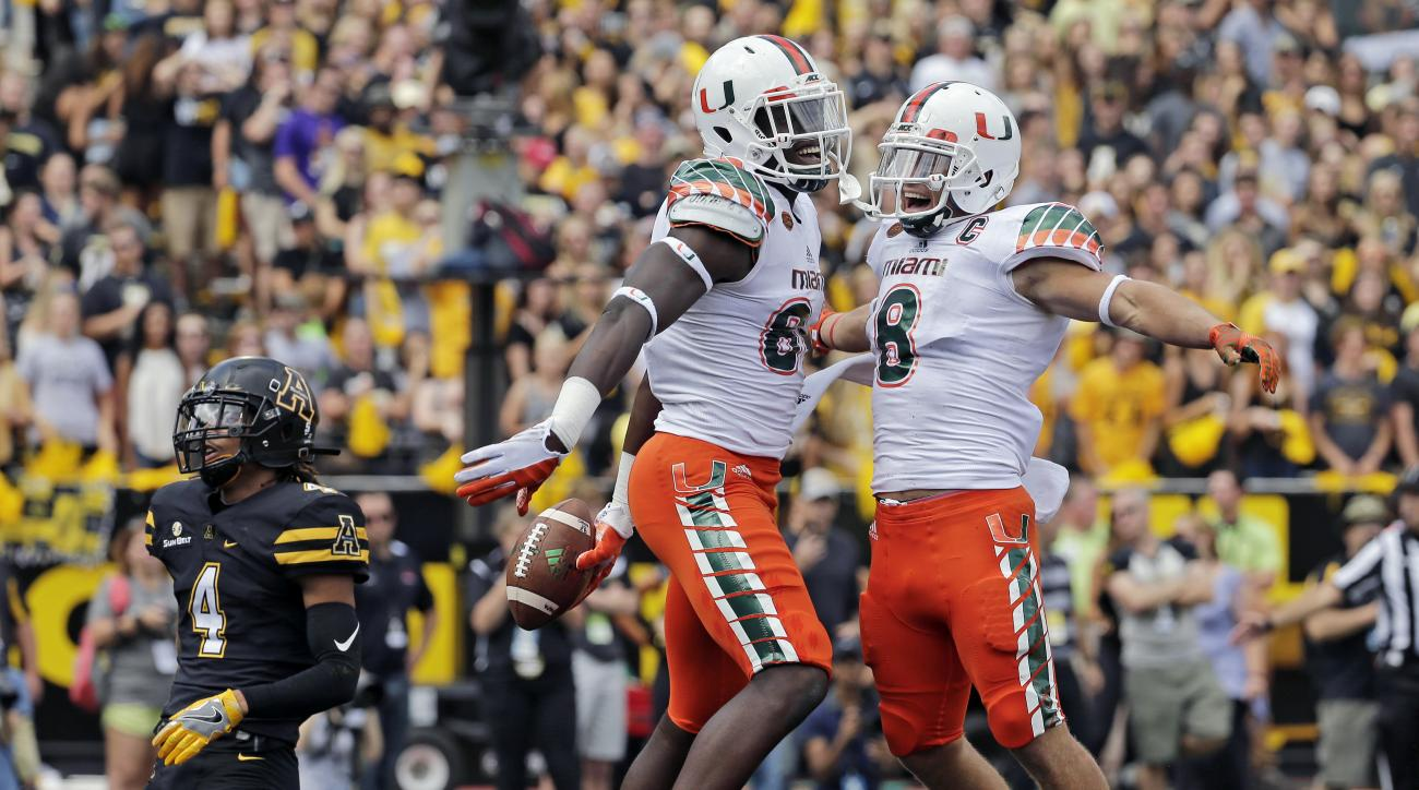 FILE - In this Sept. 17, 2016, file photo, Miami's David Njoku, center, celebrates with Braxton Berrios, right, after a touchdown catch as Appalachian State's Mondo Williams, left, watches during the first half of an NCAA college football game in Boone, N