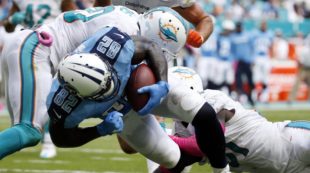 Tennessee Titans tight end Delanie Walker (82) scores a touchdown as Miami Dolphins free safety Michael Thomas (31) and free safety Reshad Jones (20) attempt to stop him, during the first half of an NFL football game, Sunday, Oct. 9, 2016, in Miami Garden