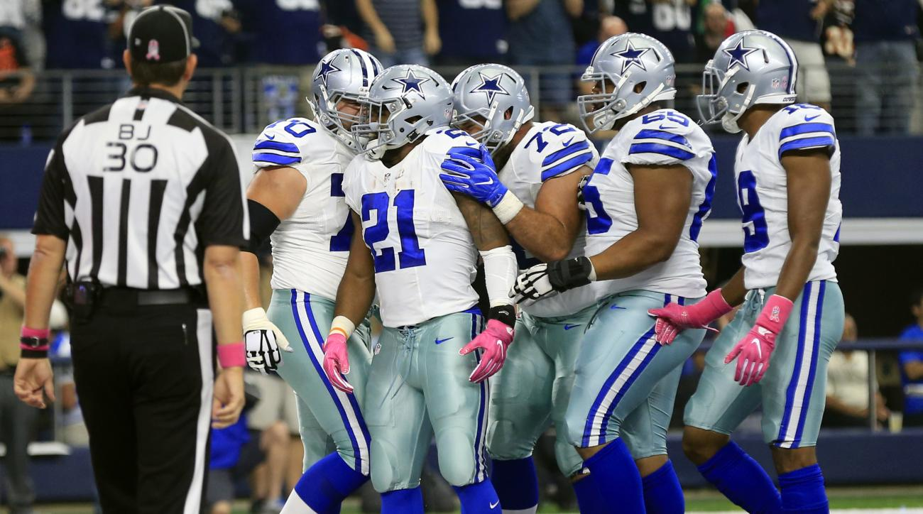 Back judge Todd Prukop (30) watches as Dallas Cowboys' Ezekiel Elliott, celebrates his touchdown run with Zack Martin (70), Travis Frederick (72), Ronald Leary (65) and Brice Butler (19) in the first half of an NFL football game against the Cincinnati Ben