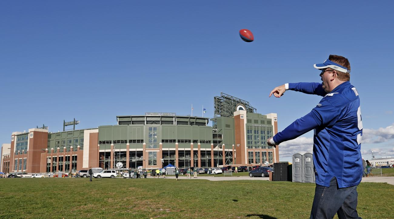 New York Giants fan Tom Leddy throws a football outside Lambeau Field before an NFL football game against the Green Bay Packers Sunday, Oct. 9, 2016, in Green Bay, Wis. (AP Photo/Matt Ludtke)