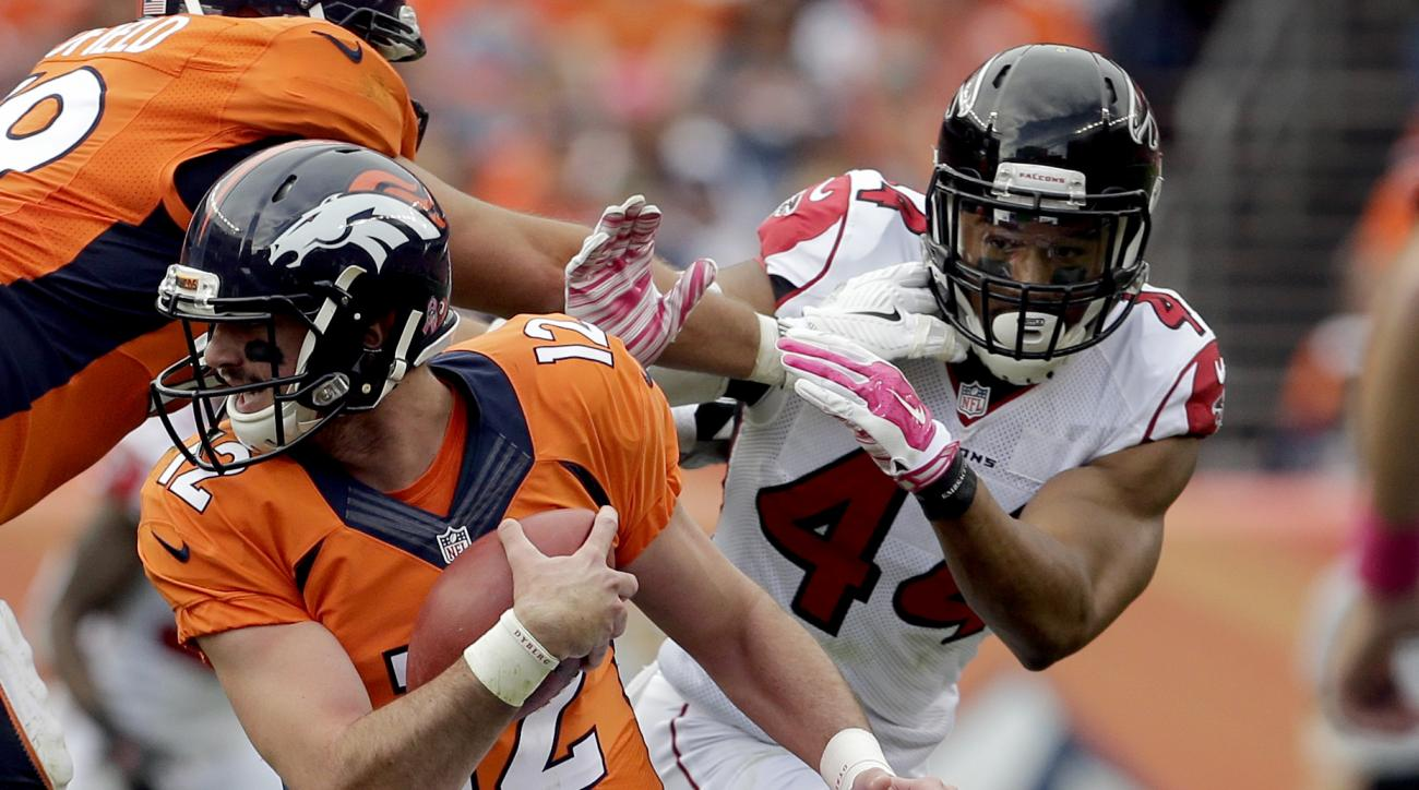 Denver Broncos quarterback Paxton Lynch (12) tries to avoid Atlanta Falcons outside linebacker Vic Beasley (44) during the second half of an NFL football game, Sunday, Oct. 9, 2016, in Denver. (AP Photo/Joe Mahoney)
