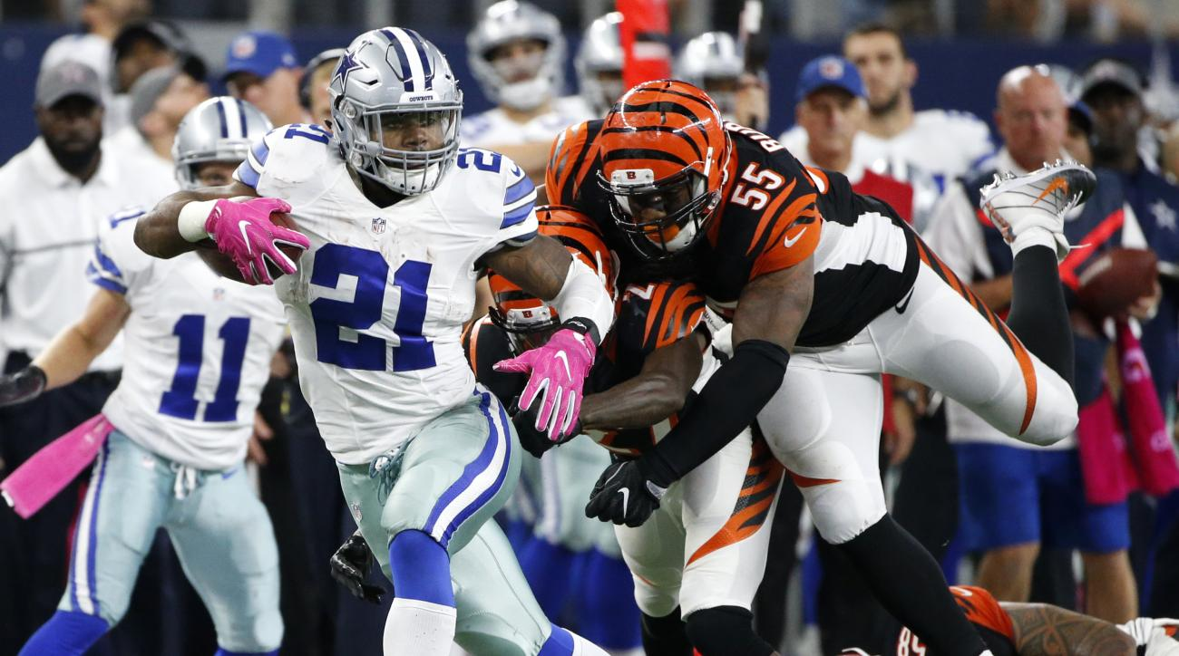 Dallas Cowboys' Ezekiel Elliott (21) evades pressure from Cincinnati Bengals' Dre Kirkpatrick (27) and Vontaze Burfict (55) in as Elliott carries the ball in the second half of an NFL football game, Sunday, Oct. 9, 2016, in Arlington, Texas. (AP Photo/Ron