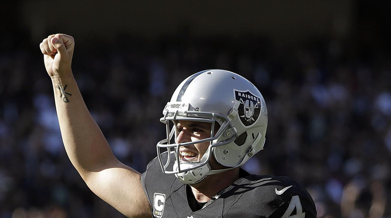 Oakland Raiders quarterback Derek Carr (4) celebrates after throwing a touchdown pass against the San Diego Chargers during the second half of an NFL football game in Oakland, Calif., Sunday, Oct. 9, 2016. (AP Photo/Marcio Jose Sanchez)