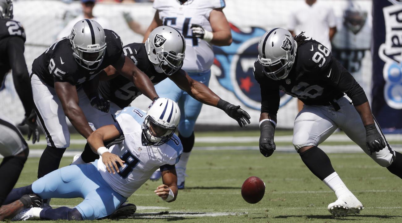 FILE -- In this Sept. 25, 2016 file photo, Tennessee Titans quarterback Marcus Mariota (8) fumbles the ball as Oakland Raiders defenders Jihad Ward (95) and Denico Autry (96) close in during an NFL football game in Nashville, Tenn. The Raiders recovered t