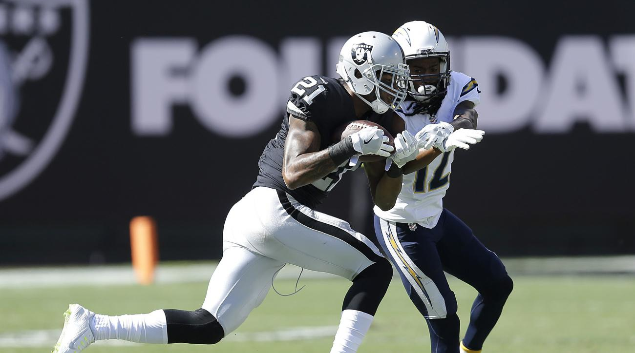 FILE - In this Oct. 9, 2016, file photo, Oakland Raiders cornerback Sean Smith (21) intercepts a pass in front of San Diego Chargers wide receiver Travis Benjamin (12) during the first half of an NFL football game in Oakland, Calif. After battling players