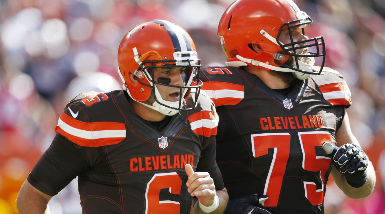 FILE - In this Oct. 9, 2016, file photo, Cleveland Browns quarterback Cody Kessler (6) walks off the field with Joel Bitonio after being injured on a hit by New England Patriots outside linebacker Dont'a Hightower in the first half of an NFL football game