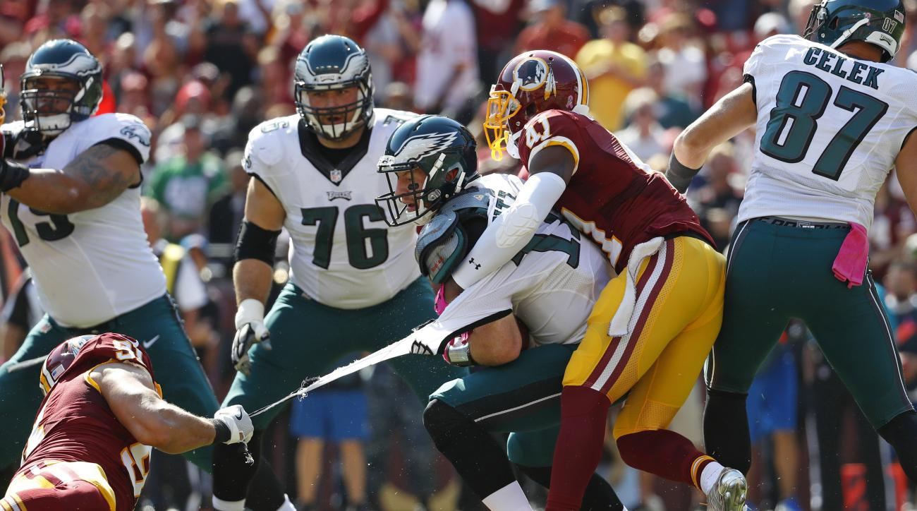 Philadelphia Eagles quarterback Carson Wentz's jersey tears as he is tackled by Washington Redskins outside linebacker Ryan Kerrigan, left, and free safety Will Blackmon in the first half of an NFL football game, Sunday, Oct. 16, 2016, in Landover, Md. (A