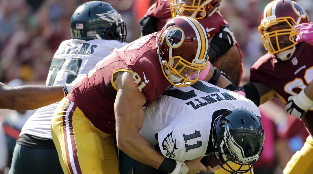 Washington Redskins outside linebacker Ryan Kerrigan, left, sacks Philadelphia Eagles quarterback Carson Wentz in the first half of an NFL football game, Sunday, Oct. 16, 2016, in Landover, Md. (AP Photo/Mark Tenally)