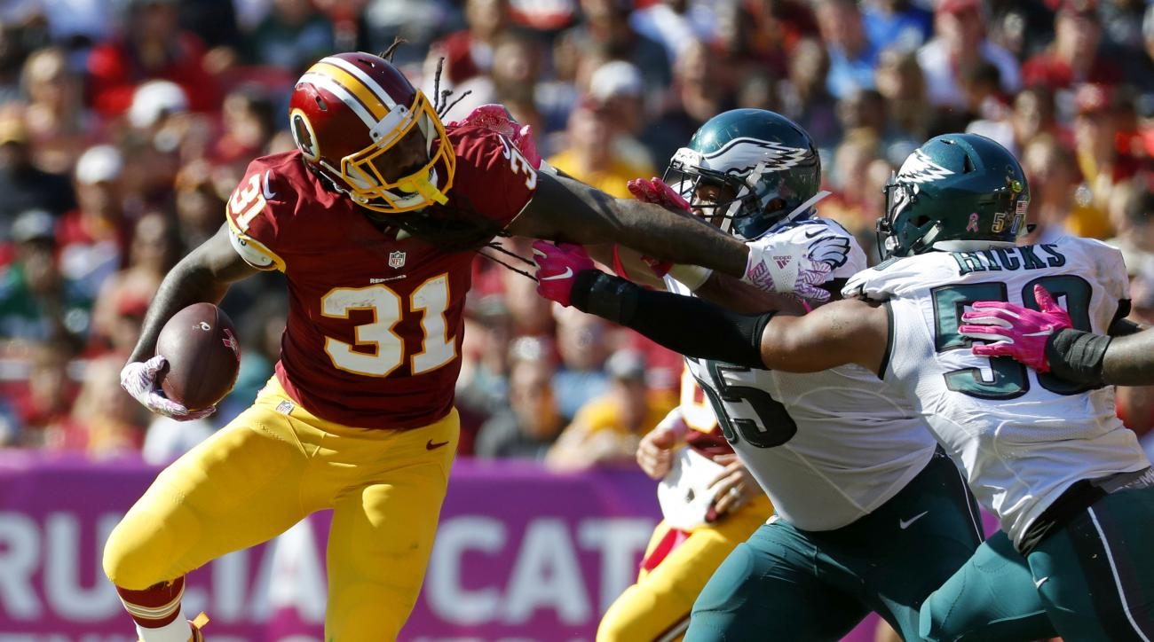 Washington Redskins running back Matt Jones, left, tries to rush past Philadelphia Eagles defensive end Brandon Graham, center, and linebacker Jordan Hicks in the first half of an NFL football game, Sunday, Oct. 16, 2016, in Landover, Md. (AP Photo/Alex B
