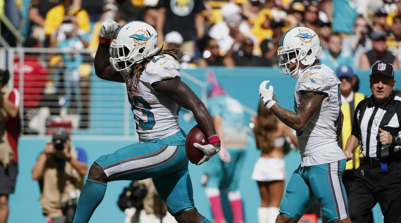 Miami Dolphins running back Jay Ajayi (23) celebrates his touchdown, during the second half of an NFL football game against the Pittsburgh Steelers, Sunday, Oct. 16, 2016, in Miami Gardens, Fla. To the right is wide receiver Kenny Stills (10).(AP Photo/Wi