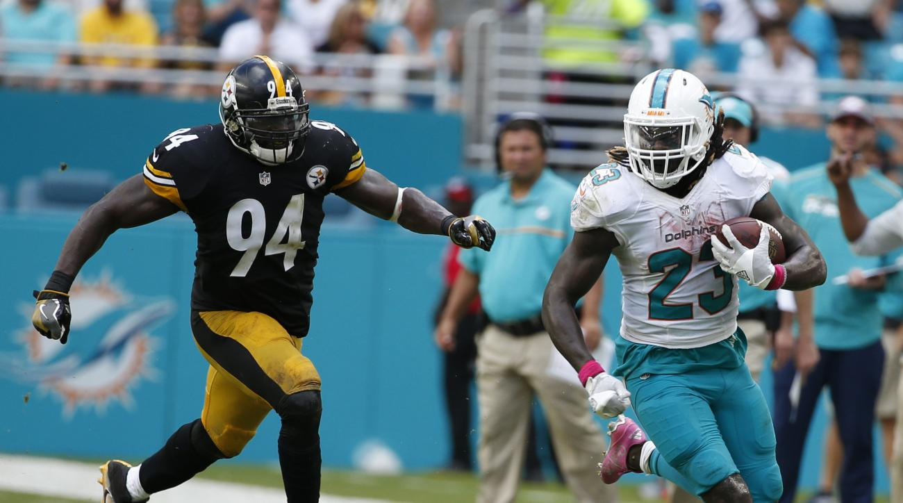 Miami Dolphins running back Jay Ajayi (23) runs ahead of Pittsburgh Steelers inside linebacker Lawrence Timmons (94), during the second half of an NFL football game, Sunday, Oct. 16, 2016, in Miami Gardens, Fla. (AP Photo/Wilfredo Lee)