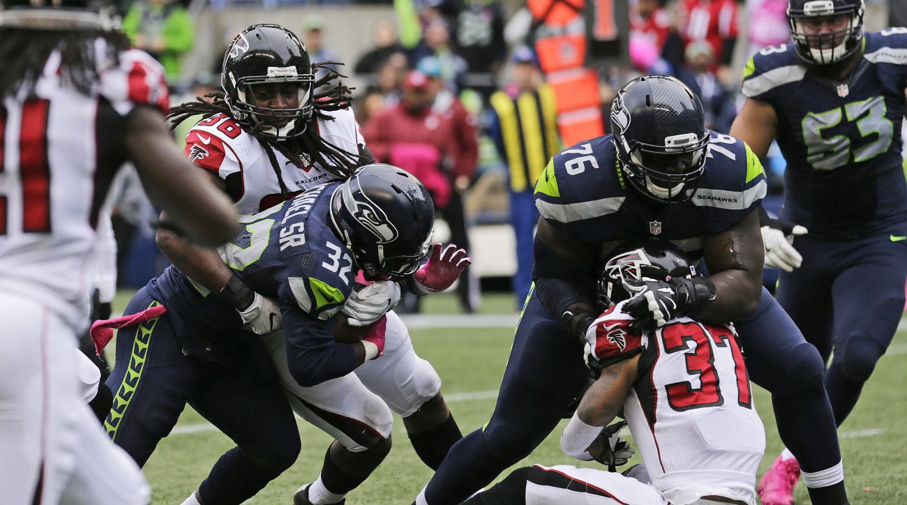 Seattle Seahawks running back Christine Michael (32) powers through a tackle attempt by Atlanta Falcons strong safety Kemal Ishmael, left, to score a touchdown in the first half of an NFL football game, Sunday, Oct. 16, 2016, in Seattle. (AP Photo/Stephen