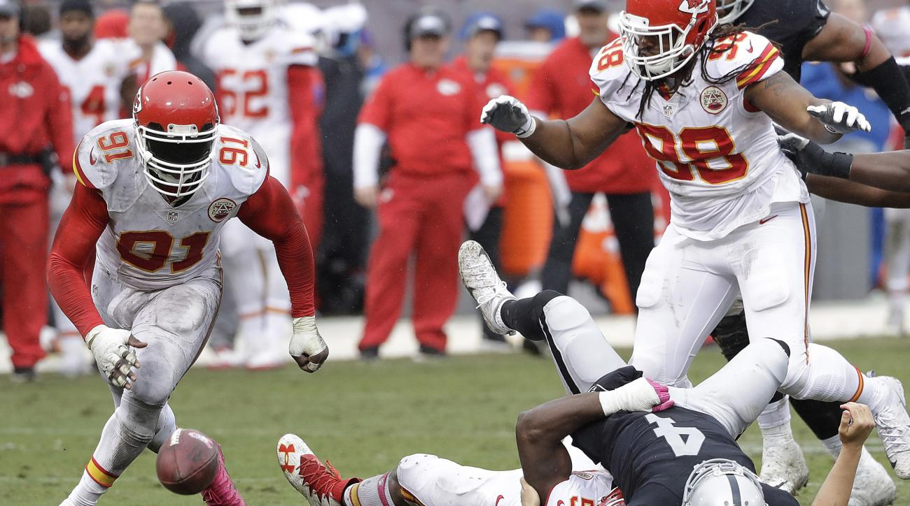 Oakland Raiders quarterback Derek Carr (4) loses a fumble as he is tackled by Kansas City Chiefs linebacker Dee Ford (55) during the second half of an NFL football game in Oakland, Calif., Sunday, Oct. 16, 2016. Chiefs outside linebacker Tamba Hali (91) r