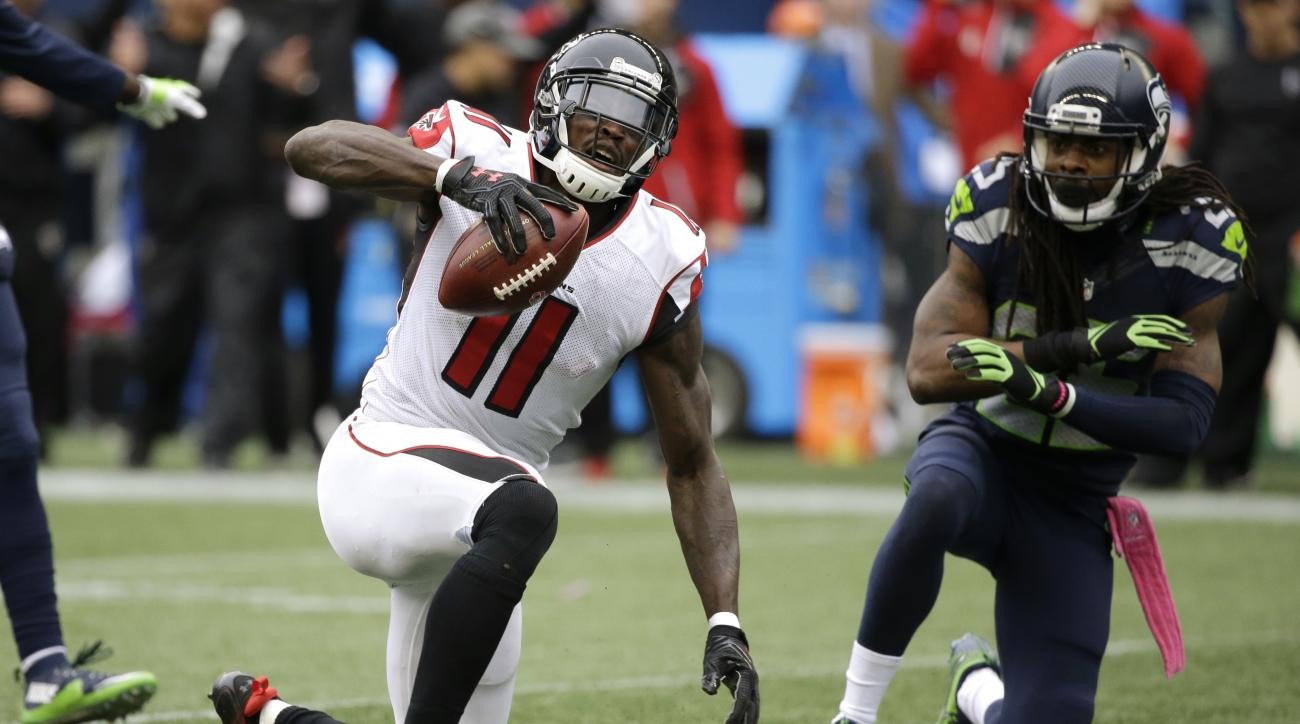 Atlanta Falcons wide receiver Julio Jones (11) reacts after Seattle Seahawks cornerback Richard Sherman, right, broke up a pass intended for him in the second half of an NFL football game, Sunday, Oct. 16, 2016, in Seattle. (AP Photo/Elaine Thompson)