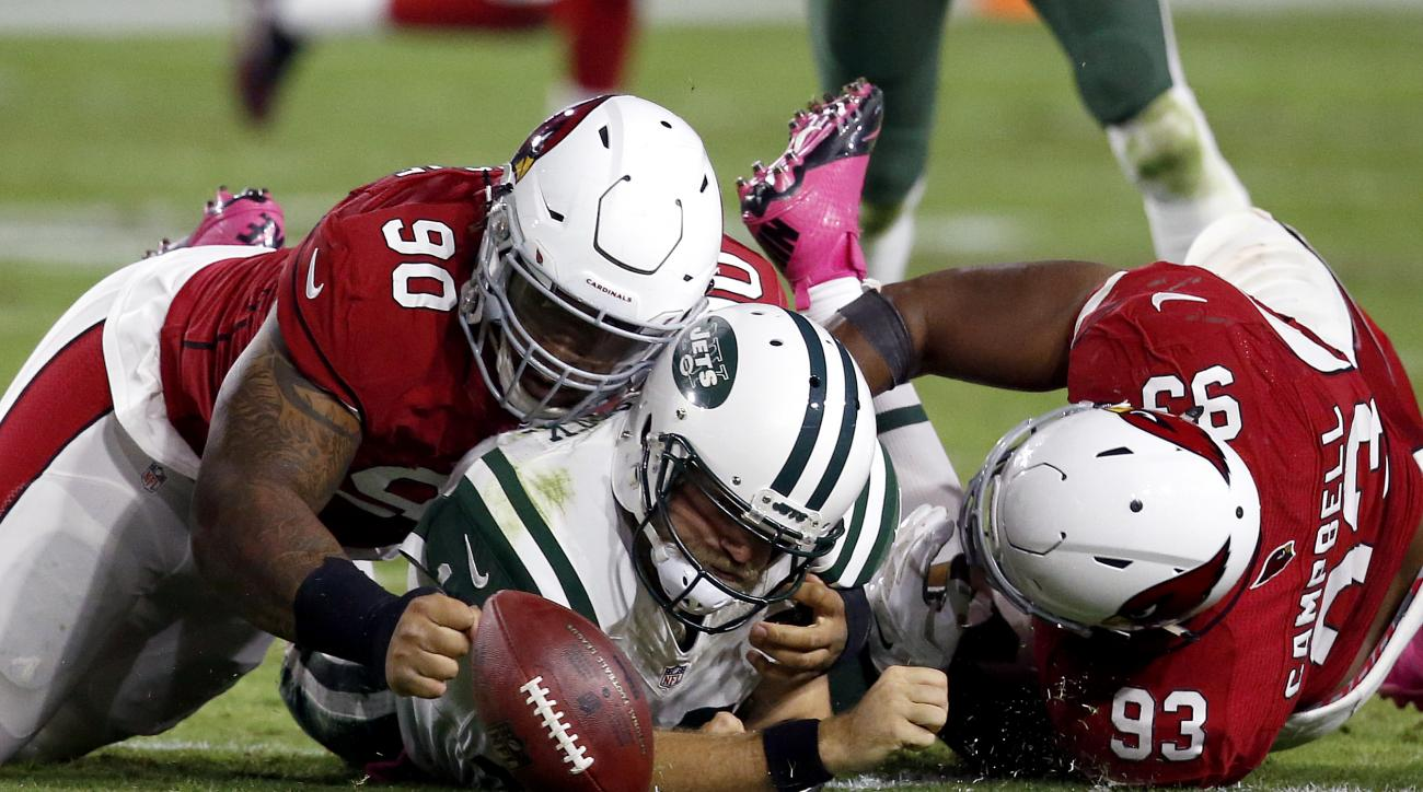 New York Jets quarterback Ryan Fitzpatrick (14) is hit by Arizona Cardinals defensive tackle Robert Nkemdiche (90) and defensive end Calais Campbell (93) during the first half of an NFL football game, Monday, Oct. 17, 2016, in Glendale, Ariz. The play was