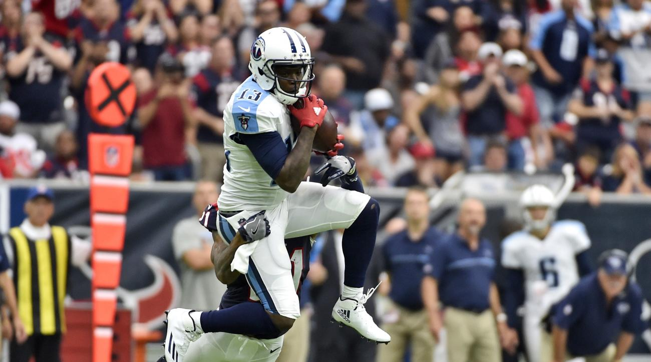 FILE - In this Oct. 2, 2016, file photo, Tennessee Titans wide receiver Kendall Wright makes a catch in front of Houston Texans cornerback A.J. Bouye (21) during the second half of an NFL football game in Houston. While his injured hamstring cost him all