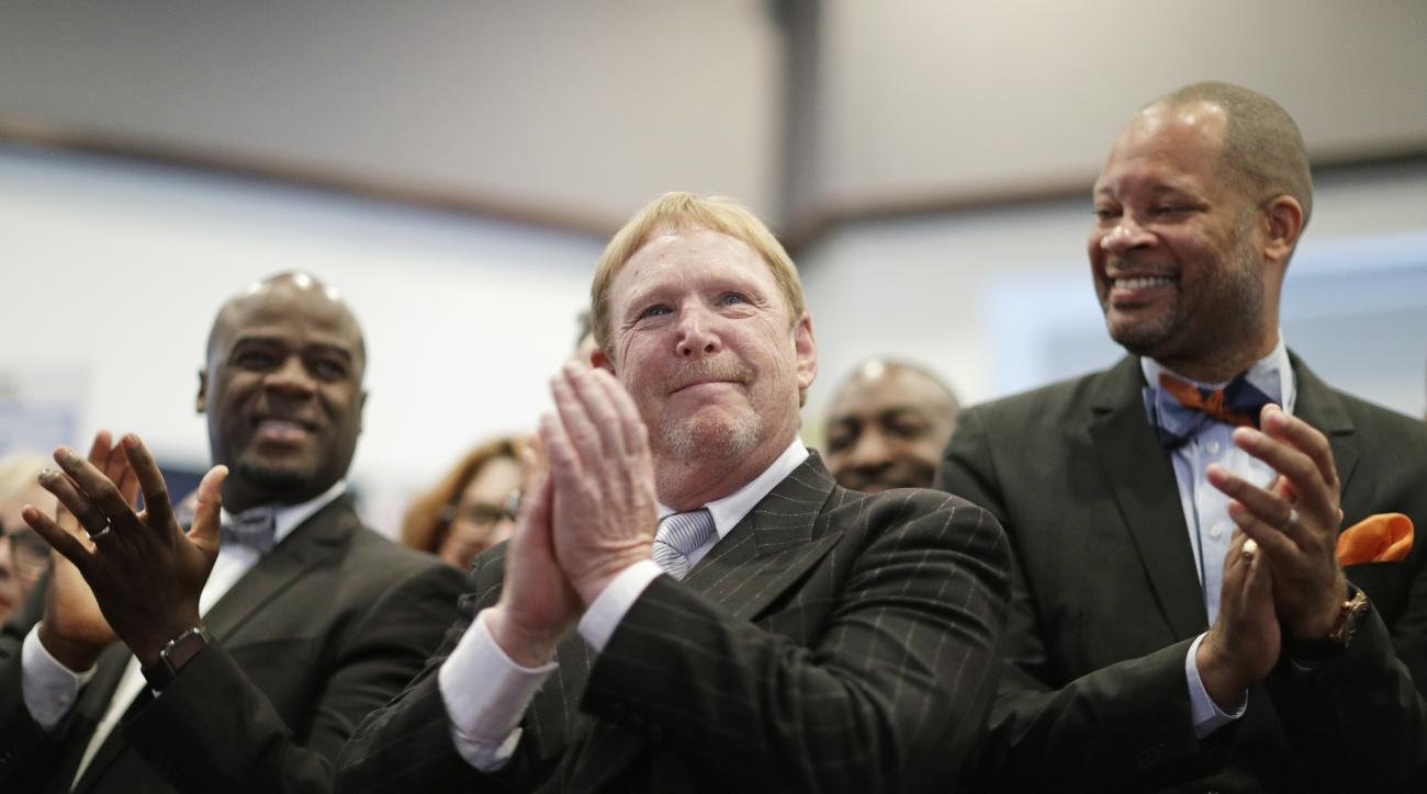 FILE - In this Monday, Oct. 17, 2016, file photo, Oakland Raiders owner Mark Davis, center, claps as he attends a bill signing ceremony with Nevada Gov. Brian Sandoval in Las Vegas. Sandoval signed a bill into law that clears the way for a Las Vegas stadi