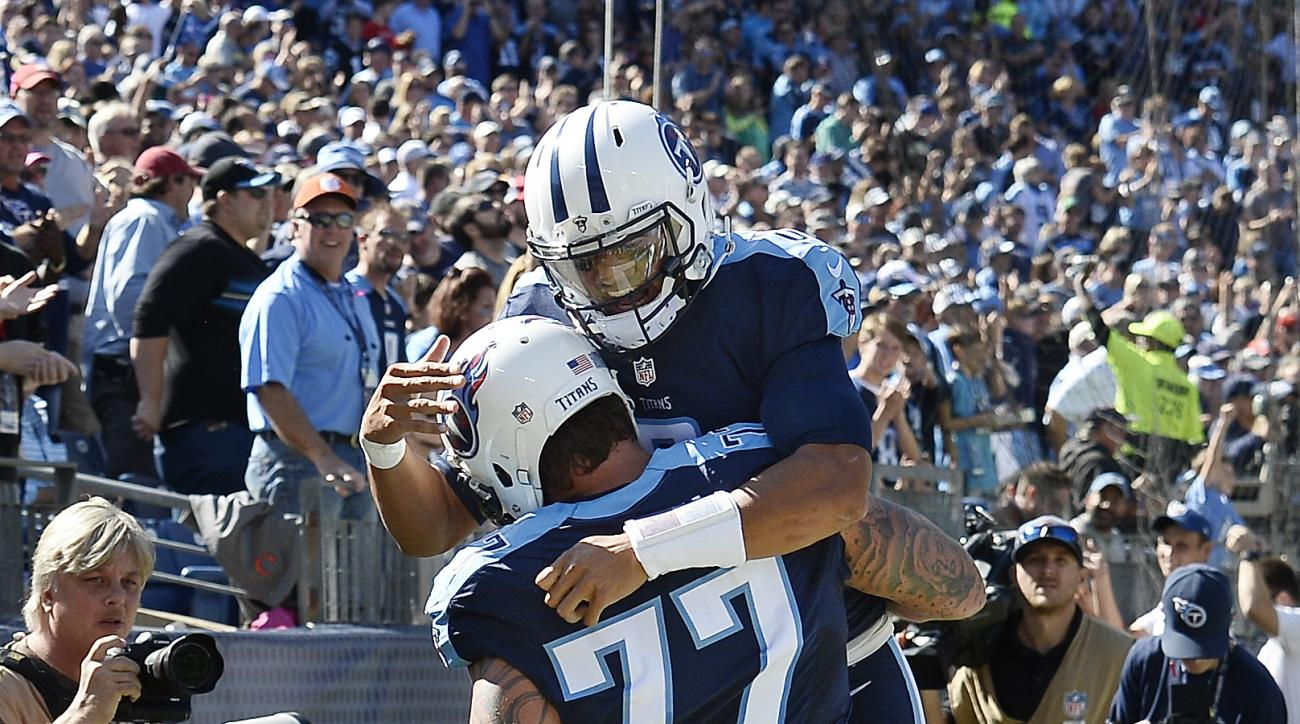 Tennessee Titans tackle Taylor Lewan (77) celebrates with quarterback Marcus Mariota after Lewan scored a touchdown on a 10-yard pass play against the Indianapolis Colts in the first half of an NFL football game Sunday, Oct. 23, 2016, in Nashville, Tenn.