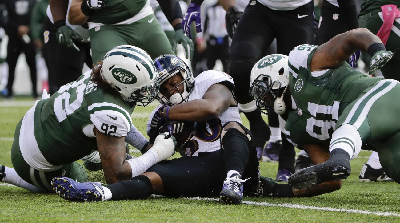 Baltimore Ravens running back Kenneth Dixon (30) is tackled by New York Jets defensive tackle Leonard Williams (92) and defensive end Sheldon Richardson (91) during the first quarter of an NFL football game, Sunday, Oct. 23, 2016, in East Rutherford, N.J.