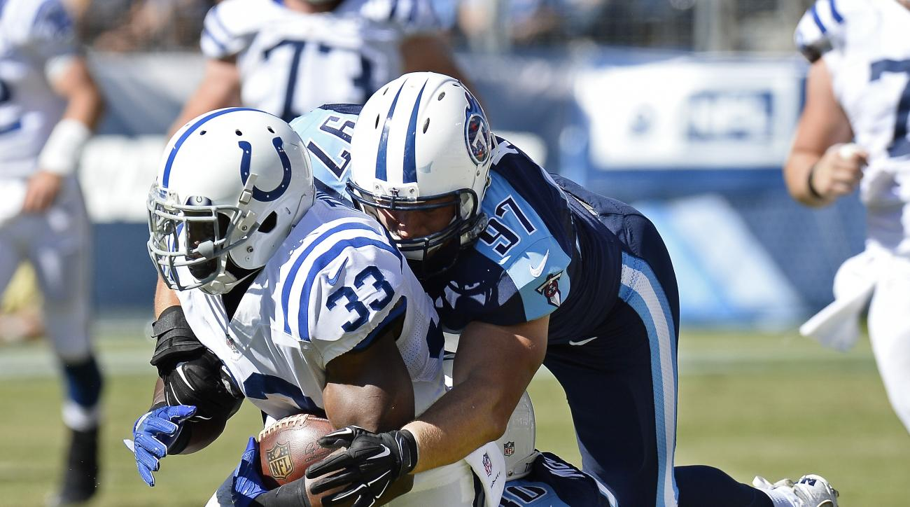 Tennessee Titans defenders Karl Klug (97) and Jason McCourty (30) try to bring down Indianapolis Colts running back Robert Turbin (33) in the first half of an NFL football game Sunday, Oct. 23, 2016, in Nashville, Tenn. (AP Photo/Mark Zaleski)