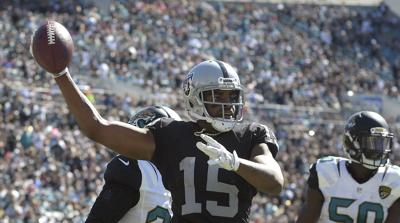 Raiders wide receiver Michael Crabtree (15) celebrates his two-yard touchdown reception in front of Jacksonville Jaguars cornerback Prince Amukamara (21) and outside linebacker Telvin Smith (50) during the second quarter of an NFL football game Sunday, Oc