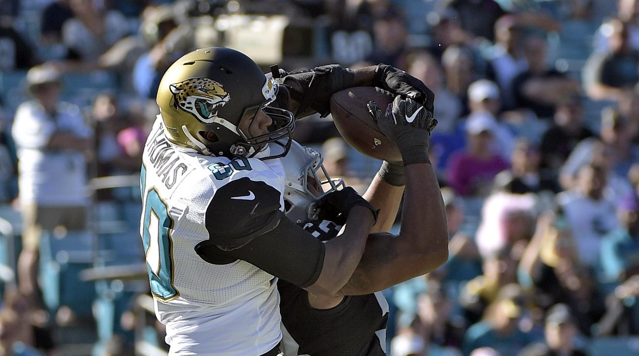 Jacksonville Jaguars tight end Julius Thomas (80) pulls in a nine-yard touchdown pass over Oakland Raiders outside linebacker Malcolm Smith during the fourth quarter of an NFL football game Sunday, Oct. 23, 2016, in Jacksonville, Fla. (AP Photo/Phelan M.