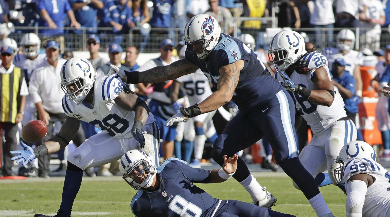 Indianapolis Colts outside linebacker Robert Mathis (98) recovers a fumble after Colts defensive tackle T.Y. McGill (99) stripped the ball away from Tennessee Titans quarterback Marcus Mariota (8) in the fourth quarter of an NFL football game Sunday, Oct.