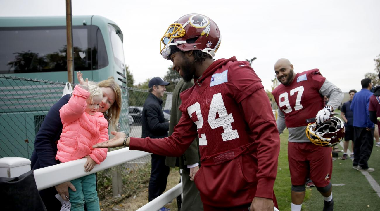 Washington Redskins' cornerback Josh Norman, 24, who is recovering from a concussion, high-fives a little girl after a training session at Wasps rugby union team training ground in west London, Friday, Oct. 28, 2016. The Washington Redskins are due to pla