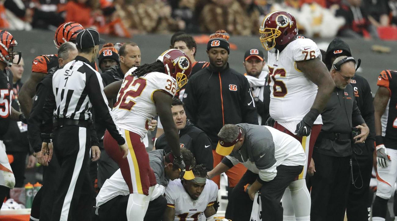 Washington Redskins wide receiver DeSean Jackson (11), center, receives treatment after being knocked over by Cincinnati Bengals free safety George Iloka (43) during an NFL Football game at Wembley Stadium in London, Sunday Oct. 30, 2016. (AP Photo/Matt D