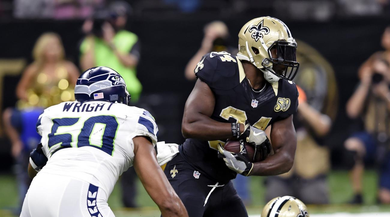 New Orleans Saints running back Tim Hightower (34) carries past Seattle Seahawks outside linebacker K.J. Wright (50) in the first half of an NFL football game in New Orleans, Sunday, Oct. 30, 2016. (AP Photo/Bill Feig)