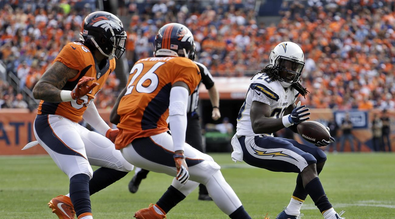 San Diego Chargers running back Melvin Gordon (28) tries to elude Denver Broncos free safety Darian Stewart (26) and linebacker Shane Ray (56) during the first half of an NFL football game, Sunday, Oct. 30, 2016, in Denver. (AP Photo/Jack Dempsey)