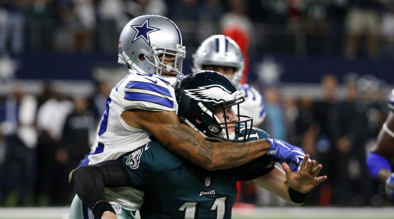 Philadelphia Eagles quarterback Carson Wentz (11) is sacked by Dallas Cowboys cornerback Orlando Scandrick, left, in the second half of an NFL football game, Sunday, Oct. 30, 2016, in Arlington, Texas. (AP Photo/Michael Ainsworth)