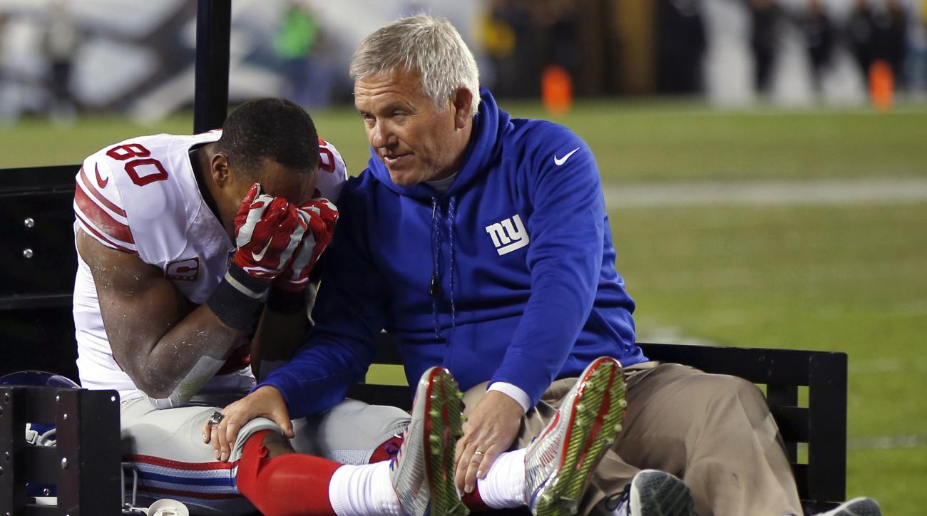 FILE - In this Oct. 12, 2014, file photo, New York Giants wide receiver Victor Cruz, left, is carted off the field during the second half of an NFL football game against the Philadelphia Eagles in Philadelphia. Playing the Eagles always had a special mean