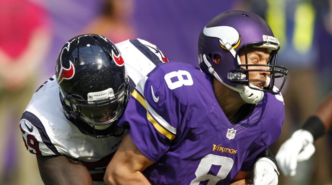 FILE - In this Oct. 9, 2016, file photo, Minnesota Vikings quarterback Sam Bradford (8) is sacked by Houston Texans outside linebacker Whitney Mercilus, left, during the first half of an NFL football game in Minneapolis. The Vikings are getting desperate
