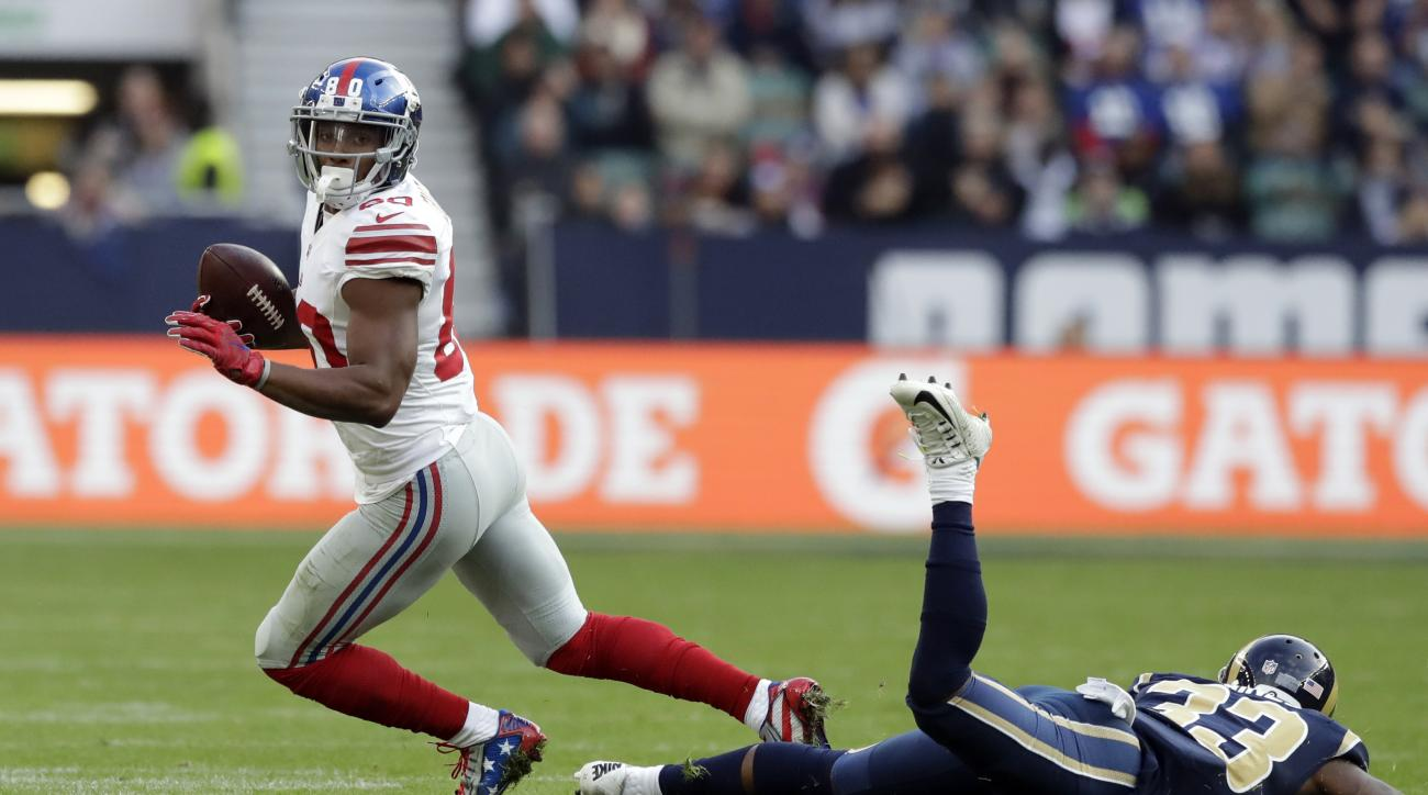 FILE - In this Oct. 23, 2016, file photo, New York Giants wide receiver Victor Cruz (80) evades a tackle by Los Angeles Rams running back Benny Cunningham (23) during an NFL football game at Twickenham stadium in London. The Giants play the Philadelphia E