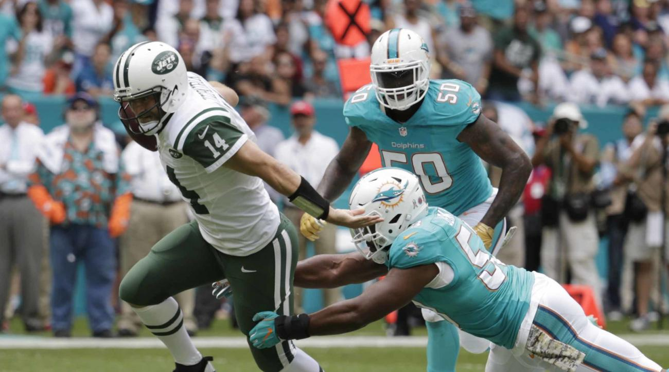 New York Jets quarterback Ryan Fitzpatrick (14) runs away from a tackle by Miami Dolphins outside linebacker Jelani Jenkins (53), during the first half of an NFL football game, Sunday, Nov. 6, 2016, in Miami Gardens, Fla. To the right is Miami Dolphins de