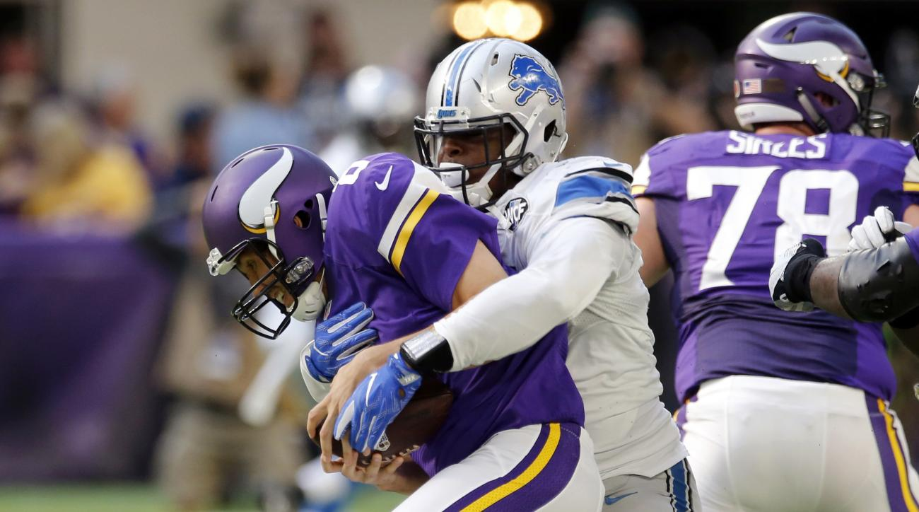 Minnesota Vikings quarterback Sam Bradford, left, is sacked by Detroit Lions defensive end Kerry Hyder during the first half of an NFL football game Sunday, Nov. 6, 2016, in Minneapolis. (AP Photo/Jim Mone)