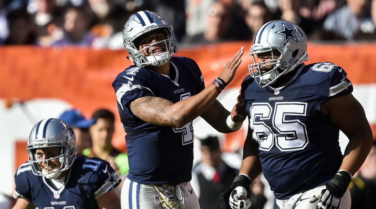 Dallas Cowboys quarterback Dak Prescott (4) celebrates a touchdown by wide receiver Cole Beasley (11) with guard Ronald Leary (65) in the first half of an NFL football game against the Cleveland Browns, Sunday, Nov. 6, 2016, in Cleveland. (AP Photo/David