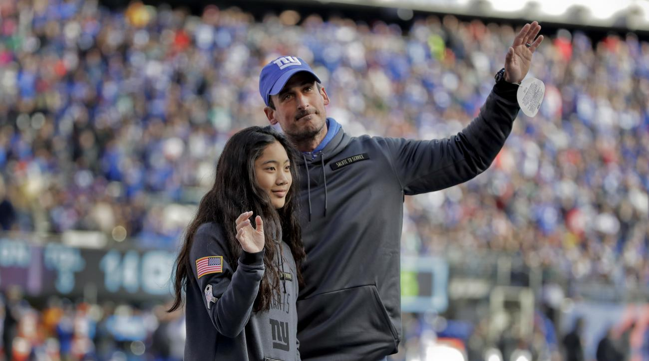 Steve DeVries, right, a combat Army medic veteran, waves as he is recognized during a timeout of an NFL football game between the New York Giants and the Philadelphia Eagles, Sunday, Nov. 6, 2016, in East Rutherford, N.J. DeVries was then presented, a pos