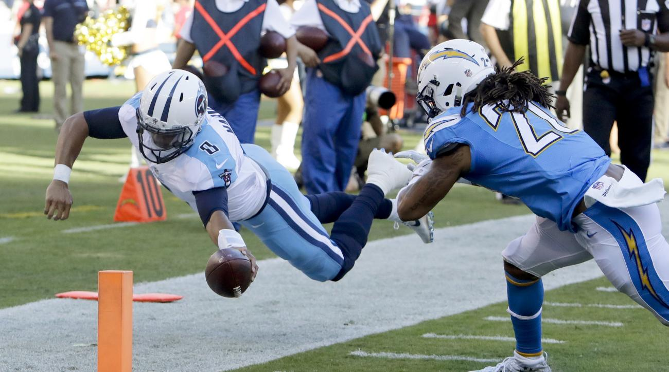 Tennessee Titans quarterback Marcus Mariota, left, dives into the end zone for a touchdown as San Diego Chargers free safety Dwight Lowery (20) defends during the second half of an NFL football game, Sunday, Nov. 6, 2016, in San Diego. (AP Photo/Rick Scut
