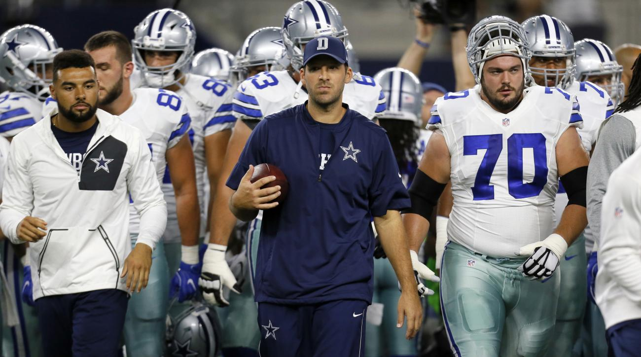 FILE - In this Oct. 30, 2016, file photo, Dallas Cowboys' Tony Romo, center, and teammates walk off the field after warm ups before an NFL football game against the Philadelphia Eagles in Arlington, Texas. Romo is running the scout team in practice even t