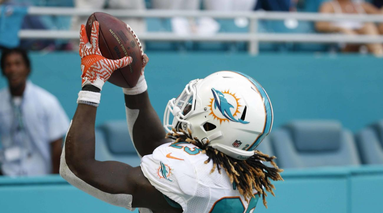 FILE - In this Sept. 26, 2016, file photo, Miami Dolphins running back Jay Ajayi catches a pass for a touchdown during overtime at an NFL football game against the Cleveland Browns in Miami Gardens, Fla. The Dolphins are 0-3 on the road as they begin a tw