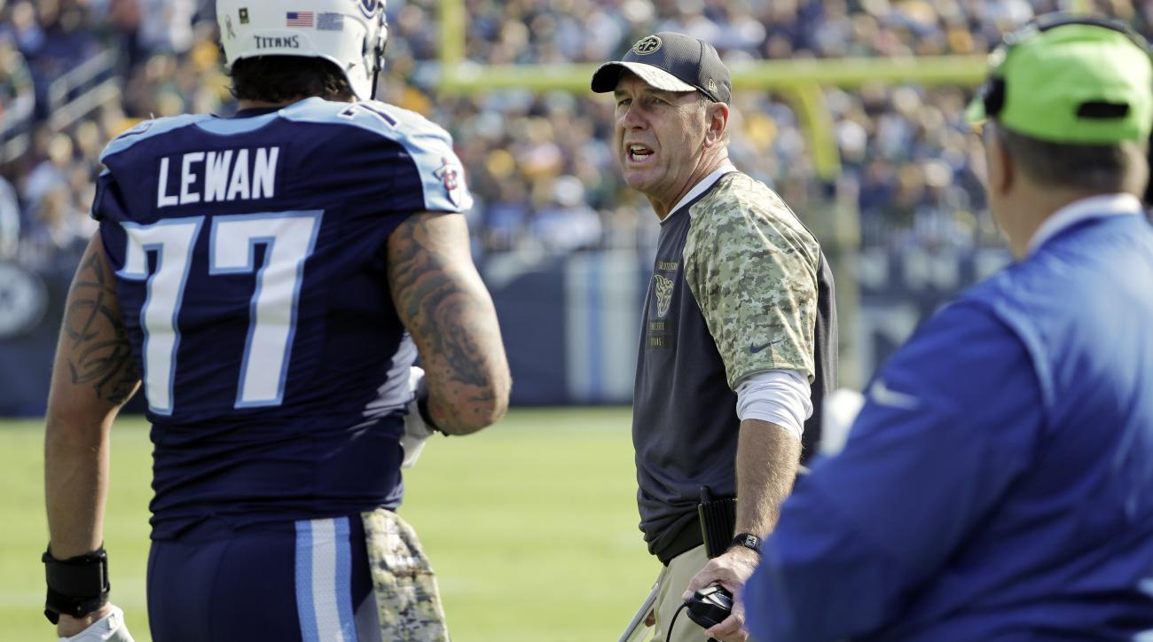 Tennessee Titans head coach Mike Mularkey talks to Tennessee Titans tackle Taylor Lewan (77) after Lewan was ejected in the first half of an NFL football game against the Green Bay Packers Sunday, Nov. 13, 2016, in Nashville, Tenn. (AP Photo/James Kenney)