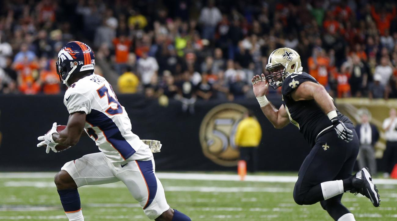 Denver Broncos defensive back Will Parks (34) grabs a blocked extra point and returns it for a safety as New Orleans Saints center Max Unger (60) pursues in the second half of an NFL football game in New Orleans, Sunday, Nov. 13, 2016. The Broncos won 25-