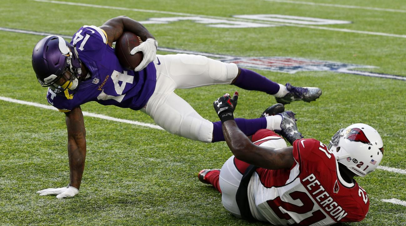 Minnesota Vikings wide receiver Stefon Diggs (14) tries to break a tackle by Arizona Cardinals cornerback Patrick Peterson, right, during the second half of an NFL football game Sunday, Nov. 20, 2016, in Minneapolis. (AP Photo/Jim Mone)